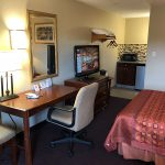 one guest bed across from work desk, chair, mirror, TV, dresser, microwave, and ottoman at Travel Inn & Suites