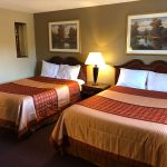 two guest beds with nightstand between at Travel Inn & Suites