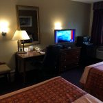 two bed ends across from TV, work desk, dresser, microwave, and mini fridge at Travel Inn & Suites