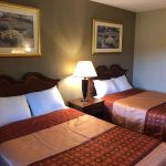 two guest beds with nighstand in between at Travel Inn & Suites